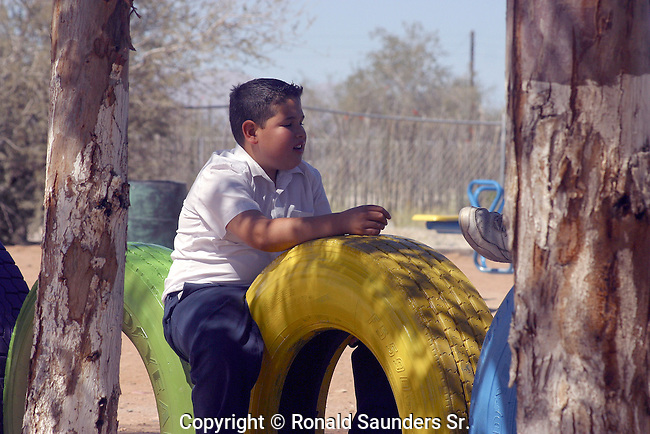 SCHOOLBOY SITS ON TIRES IN SCHOOL YARD