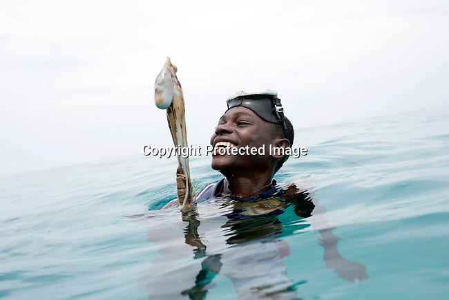 PEMBA, TANZANIA - DECEMBER 7 : Hamissi Usi, age 15, holds an octopus on December 7, 2010 on Pemba, Tanzania. He works as a fisherman. He doesn't go to school but lives with his parents and siblings in the small village of Tumbe. (Photo by: Per-Anders Pettersson)