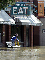 Findlay resident Tom Holmes sits on a bench on Main Street as flood waters from the Blanchard River start to recede after heavy rains caused flooding Thursday, August 23, 2007, in Findlay, Ohio. The Blanchard River was close to 7 feet above flood stage at Findlay yesterday morning, the highest since a 1913 flood.