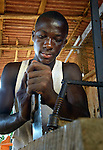 Anthony Logan at work in a carpenter's shop in Buchanan, Liberia. The young man is a graduate of the skills training program at the Brighter Future Children Rescue Center in Buchanan. Supported by the United Methodist Church in Germany and United Methodist Women, the center carries out rehabilitation work with ex-combatants and other war-affected children.