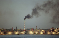 Industrial scene with chimney emitting smoke by the riverside in Havana; Cuba,