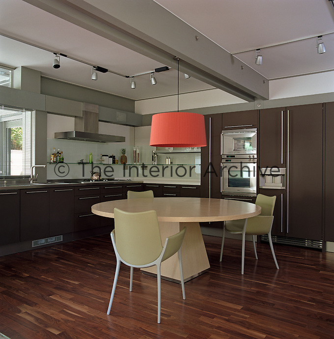 A red pendant light is suspended over the large round dining table in the centre of this modern kitchen