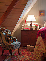An ambient glow from a bedside lamp illuminates a cheerful corner of this attic bedroom