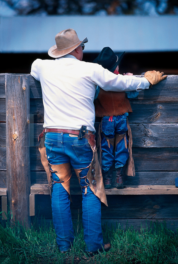 Rear view of two generations of cowboys as they look over a corral fence. South Dakota.