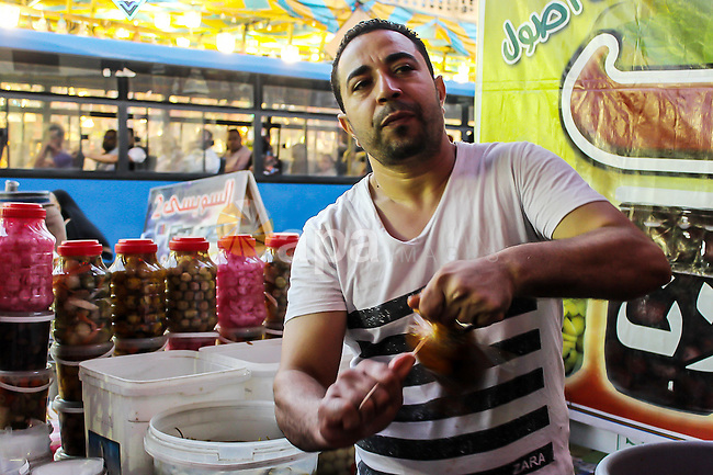 An Egyptian vendor sells pickles at a street market on the holy month of Ramadan, in the Cairo, Egypt, on June 23, 2016. Ramadan is sacred to Muslims because it is during that month that tradition says the Koran was revealed to the Prophet Mohammed. The fast is one of the five main religious obligations under Islam. More than 1.5 billion Muslims around the world will mark the month, during which believers abstain from eating, drinking, smoking and having sex from dawn until sunset. Photo by Amr Sayed