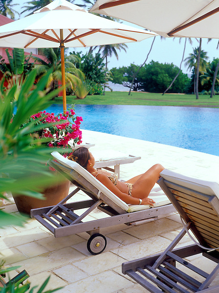 Woman sunbathing by pool at the Cap Est Lagoon Resort and Spa. Le Francois, Martinique.