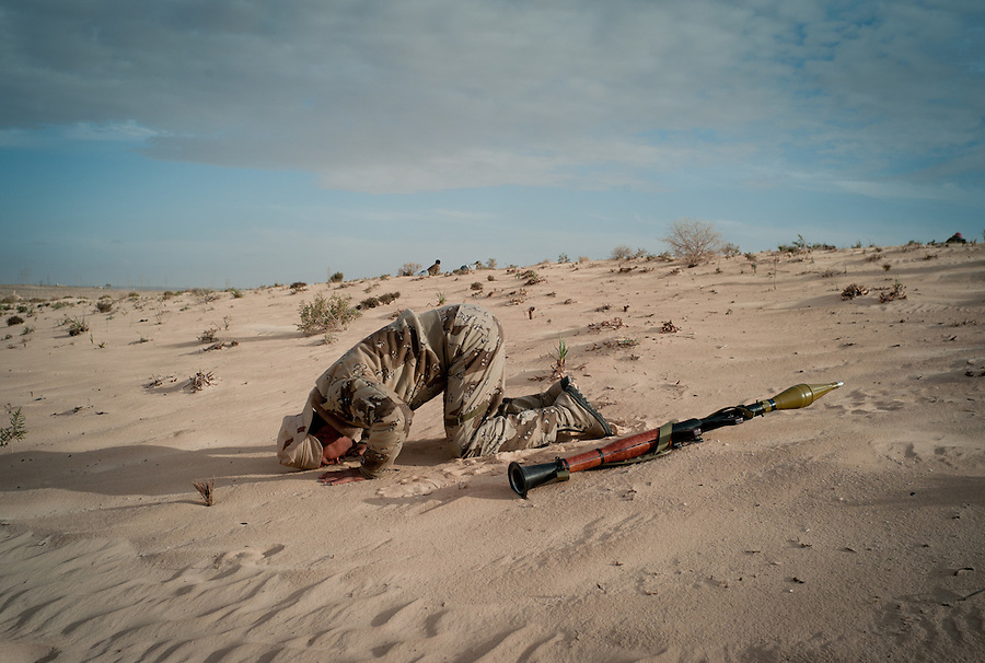 Rebel fighter prays in the sand with his RPG in Ajdabiya, Libya.