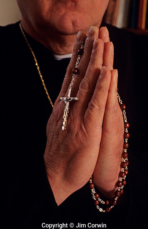 Man in priest costume in prayer holding rosary with crucifix showing close-up on hands