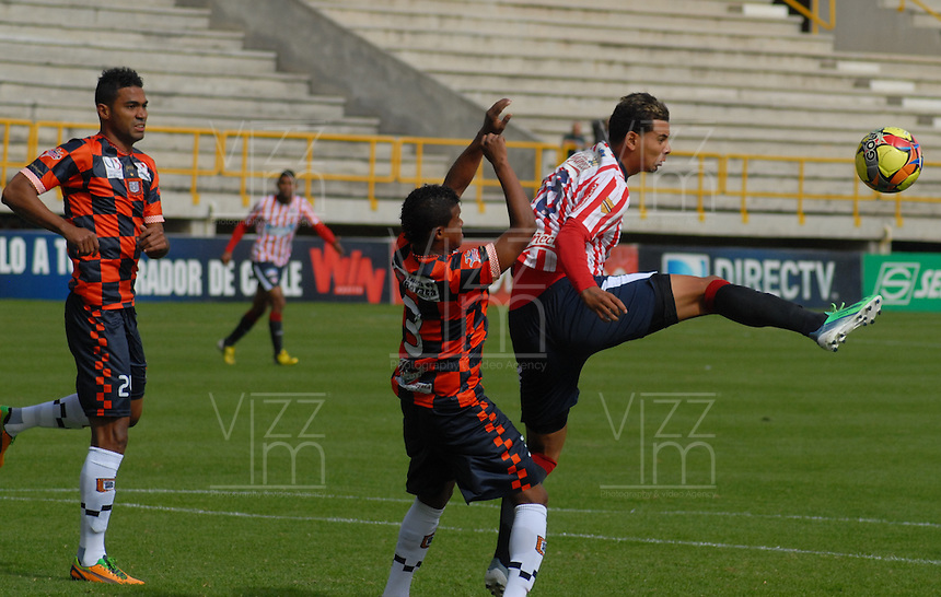 TUNJA -COLOMBIA. 11-08-2013. Andres Sarmiento (I) de Chico disputa el balón con Edwin Cardona (D) de Junior durante partido de la fecha 3 de la Liga Postobón II 2013 jugado en el estadio la Independencia de la ciudad de Tunja./ Chico Andres Sarmiento (L) fights for the ball with Junior Edwin Cardona (R) during match on the 3th date of the Postobon League II 2013 at  Independencia  stadium in Tunja city. Photo: VizzorImage / Jose Miguel Palencia/ Str