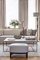 A living room furnished with a sofa and soft furnishings in neutral tones. A leather stool and metal coffee table sit on a rug over a parquet floor.