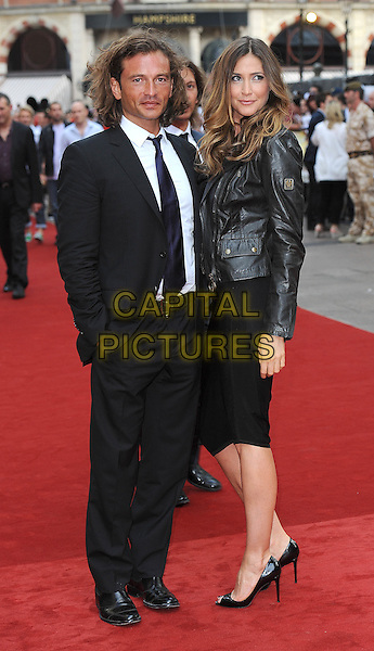"""MANUELE MALENOTTI & LISA SNOWDON.""""The Expendables"""" UK Film Premiere, Odeon Leicester Square, London, England..August 9th, 2010.half length black dress open peep toe shoes patent Christian Louboutin leather jacket side suit .CAP/BEL.©Tom Belcher/Capital Pictures."""