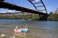 Two sexy females on water floats in the turquoise waters of Lake Austin at the Loop 360 Bridge Park Beach during a blistering hot Texas summer.