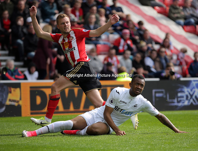 (L-R) Seb Larsson of Sunderland is tackled by Jordan Ayew of Swansea City during the Premier League match between Sunderland and Swansea City at the Stadium of Light, Sunderland, England, UK. Saturday 13 May 2017