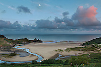 A few miles outside of Swansea, Wales along very narrow roads is a beach overlook at the Three Cliffs camping site.  This was taken at sunset.  The moon reflection can be seen in the stream at the bottom of the photo.