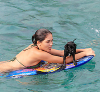 A young woman and a black puppy balance on a boogie board in Kailua-Kona, Hawai'i Island.