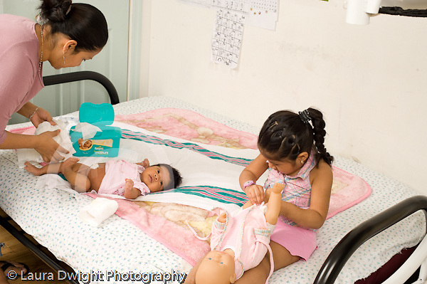 newborn baby girl one month old  Mexican American with mother diaper change while 3 year old sister plays with doll nearby modeling imitation horizontal
