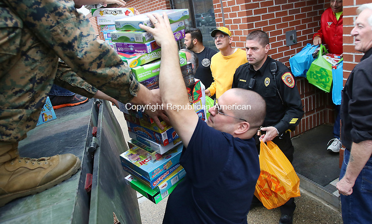 WOLCOTT CT. 14 December 2015-121415SV03-Darryl Lanzara of Wolcott, center, along with other volunteers load toys into a truck, for Toys for Tots, at Wolcott Police Department in Wolcott Monday. Toys collected went to Toys for Tots, Wolcott Needy Services, Social Services in Watertown, Connecticut Children&rsquo;s Medical Center, and the Brass City Memorial Detachment of the Marine Corp. League. <br /> Steven Valenti Republican-American
