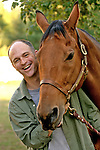 Mid adult man standing with horse, smiling