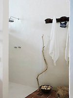 A simple whitewashed shower cubicle is situated at one end of the bathroom