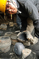 "Opening a cast containing an iron kettle, Oigen ""Nambu Tekki"" ironware foundry, Esashi, Iwate Prefecture, Japan, August 28 2008."