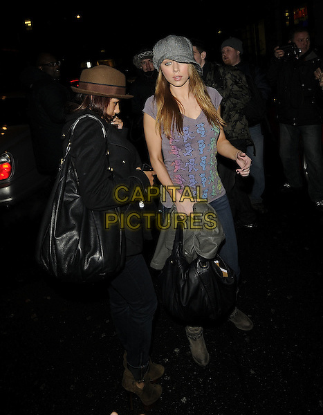 VANESSA WHITE & UNA HEALY Of The Saturdays.At the Mayfair Hotel, London, England, UK, 16th January 2010..full length denim skinny jeans grey gray bag  cap hat t-shirt brown bag back coat side suede boots .CAP/CAN.©Can Nguyen/Capital Pictures
