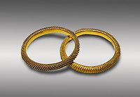 Bronze Age Hattian gold bracelet  from a possible Bronze Age Royal grave (2500 BC to 2250 BC) - Alacahoyuk - Museum of Anatolian Civilisations, Ankara, Turkey. Against a gray background