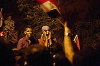 EGITTO, IL CAIRO 9/10 settembre 2011: assalto all'ambasciata israeliana. Migliaia di manifestanti egiziani, ancora infuriati per l'uccisione di cinque guardie di frontiera egiziane da parte dell'esercito israeliano, hanno fatto irruzione nella sede diplomatica israeliana e sono stati poi sgomberati da esercito e polizia egiziana. Nell'immagine: giovani manifestanti la sera della protesta. Dietro di loro alcuni poliziotti egiziani.<br /> Egypt attack to the Israeli embassy  Attaque &agrave; l'ambassade israelienne Caire