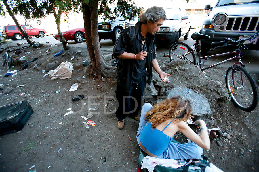 A local drug addict named Ricky offers money for drugs from a prostitute at one of the main shooting galleries for intravenous drug-users in downtown Victoria, British Columbia, BC, Canada. Photo shot for the NATIONAL POST.