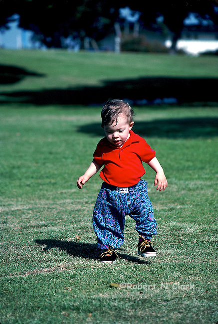 Young boy in park walking toward camera, looking at the ground with his foot raised