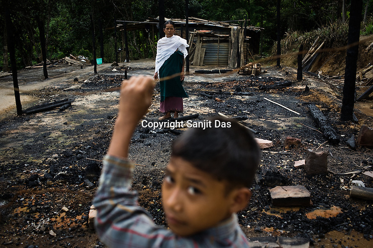 One of the victims of ethnic violence, Ronsomo Langthasa poses in front of her burnt house while her son Sanjit looks on in Jorai village. Ethnic clashes are regularly taking place between Zeme Nagas and the Dimasa tribe in North Cachar Hills in Assam, India. On 8th May 200, suspected Zeme Naga groups attacked a Dimasa village and burnt down 10 out of 13 houses. In this act of violence, they spared the school and the community centre, where most of the families are taking shelter.