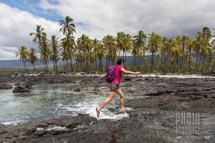 A visitor jumps over the incoming tide at Pu'uhonua o Honaunau in Kona, Hawai'i Island.