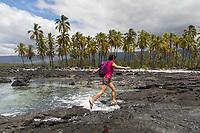 A visitor jumps over the incoming tide at Pu'uhonua o Honaunau in Kona, Hawai'i Island.
