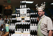 May 26, 2010. Durham, North Carolina.Employee poses wearing Best of the Triangle 2010 crown in front of wine bottle display..Employee poses during Wine Authorities, wine tasting event.