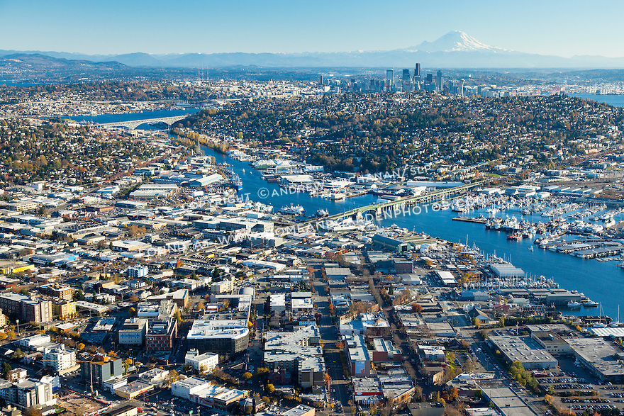 Aerial photo of Lake Washington Ship Canal, Ballard neighborhood (foreground), Fremont neighborhood (middle left), and Queen Anne Hill (middle right), with the Seattle skyline and Mount Rainier in the background