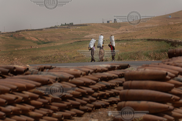 Women with sacks of collected scrap metal walk past piles of UXOs (unexploded ordnances).