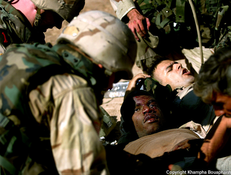 Two 1st Infantry Division soldiers receive medical attention at the scene where an IED detonated near Baqubah, Iraq on July 5, 2004.  (photo by Khampha Bouaphanh)