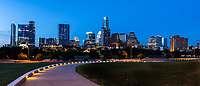 Image at dusk as this lighted path which leads the way to a view of Austin skyline as a  backdrop from the Long Center in this panorama image.   The Long is a favorite place to capture an image of Austin skyline so much so it almost impossible to capture it without a crowd.  The city of Austin has been growing at leap and bound and there are so many new high-rise skycrapers coming to the downtown area.  Most of the new high rise buildings are along Lady Bird lake which makes for some great skyline views. You can still see one of our first high rise buildings the Frost Bank building along with tallest building the Austonian at least for now. The Independence is being built now and will be tallest building but till then the Austonian will have the title.  The architecture of Austin tends to be on the modern side and there are many new building that  are on their way like the Independence or Jingle building which will seem to defy gravity which push the city architecture to be even more of a modern city when it is finished in two years.