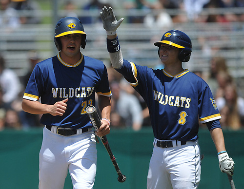 Brian Morrell #23, Shoreham-Wading River pitcher, left, gets a congratulatory pat on the back from teammate Alex Bettenhauser #8 after crossing home plate in the Class A varsity baseball Long Island Championship against Wantagh at SUNY Old Westbury on Saturday, June 3, 2017.