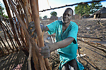 A woman fastens sticks together to build a hut in the Rhino Refugee Camp in northern Uganda. As of April 2017, the camp held almost 87,000 refugees from South Sudan, and more people were arriving daily. About 1.8 million people have fled South Sudan since civil war broke out there at the end of 2013. About 900,000 have sought refuge in Uganda.