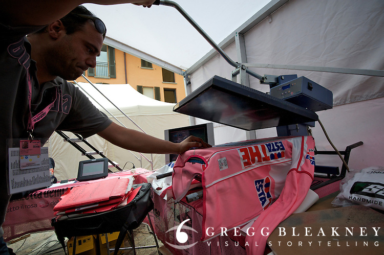 Alberto Contador's fresh Maglia Rosa--team badges are pressed onto race leader's jerseys at the end of each stage in a restricted access tent behind the podium.