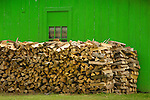 Woodpile in front of green shed.