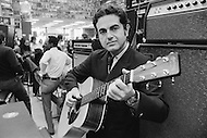 May 5th,1972. French, Egyptian born, composer and singer Guy Béart testing guitars in a music shop in New York. Image by © JP Laffont