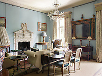 The sitting room is decorated in a cool blue with traditional furnishings and the George I marble chimneypiece provides an impressive focal point. At the window are curtains in Hardwick Green by Robert Kime for Chelsea Textiles.