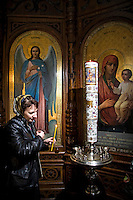 LETTLAND.Riga, 04.2009.Die neue Multireligiositaet: Anna, russisch-orthodox, beim Kirchenbesuch..© Reinis Hofmanis/EST&OST.Anna, Latvian Orthodox Congregation:.The prayer is a conversation. It can be God or the Holy Virgin, or any of the saints, or the guardian angel. Address Him with a request for help or a prayer of your gratefulness that your previous prayer has been answered. You can confide in him like in your relation with your sorrows, contemplations, joys and troubles. It is the most intimate conversation. We address particular saints on particular occasions. In any case, when a man turns with a sincere prayer to God or to the saints, usually sooner or later the prayer is answered. We pray for ourselves and for our relations, for the living and the dead.
