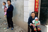 China. Province of Henan. Village Xiaotan. Portrait of a seated grandmother holding her granddaughter in her arms. A father who is a neighbour holds his son in his arms. A good example of the chinese family and the one child policy. © 2004 Didier Ruef