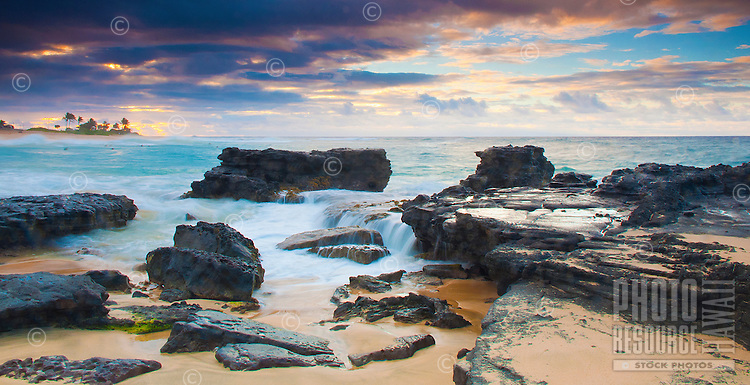 Sandy Beach in East O'ahu, just after sunrise, with water softly flowing over rocks.