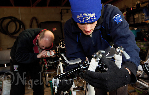 10 DEC 2011 - NORFOLK, GBR - Guide Luke Watson (right) tightens the bolts on his tribars as Iain Dawson (left) tapes up his handlebars as they set up the new tandem for a ride during one of the few training weekends they will have together before the start of the new season (PHOTO (C) NIGEL FARROW)