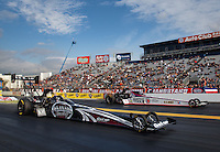 Feb 7, 2014; Pomona, CA, USA; NHRA top fuel dragster driver Shawn Langdon (near) races alongside Antron Brown during qualifying for the Winternationals at Auto Club Raceway at Pomona. Mandatory Credit: Mark J. Rebilas-