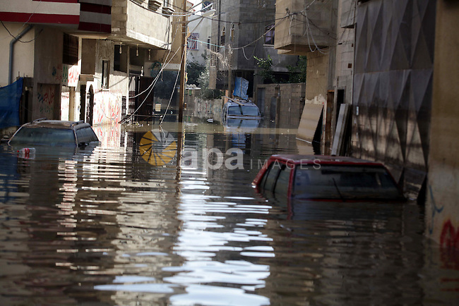 Cars are seen float in rainwater in Al Sheikh Redwan area that was flooded in Gaza City, 18 December 2013. Four days of torrential rains in Gaza Strip killed two people and forced the evacuation of more than 5,000 residents from flooded homes, some accessible only by boat, officials said. Photo by Ashraf Amra