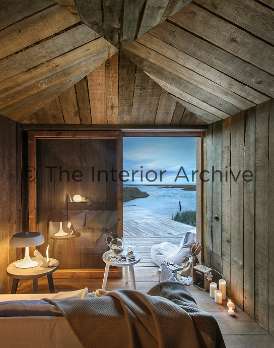 The interior of the living room cabin is furnished with a Ghost sofa by Paola Navone and a sliding glass door opens onto a pontoon which extends over the estuary